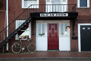 Red brick store front of the Old As Adam shop in downtown Portsmouth, New Hampshire, with a bicycle