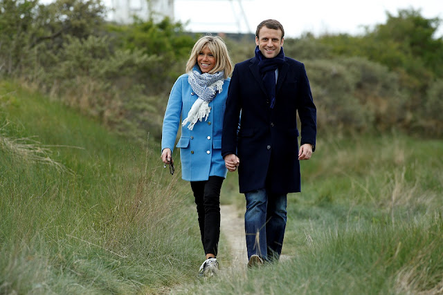 Man and a woman striding along a path through a field