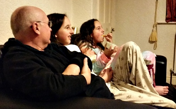 My family sat on the sofa snacking. My fella and two girls.