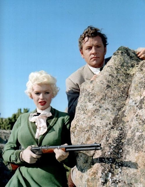 Jayne Mansfield holding a gun, while Kenneth More peers from behind a rock