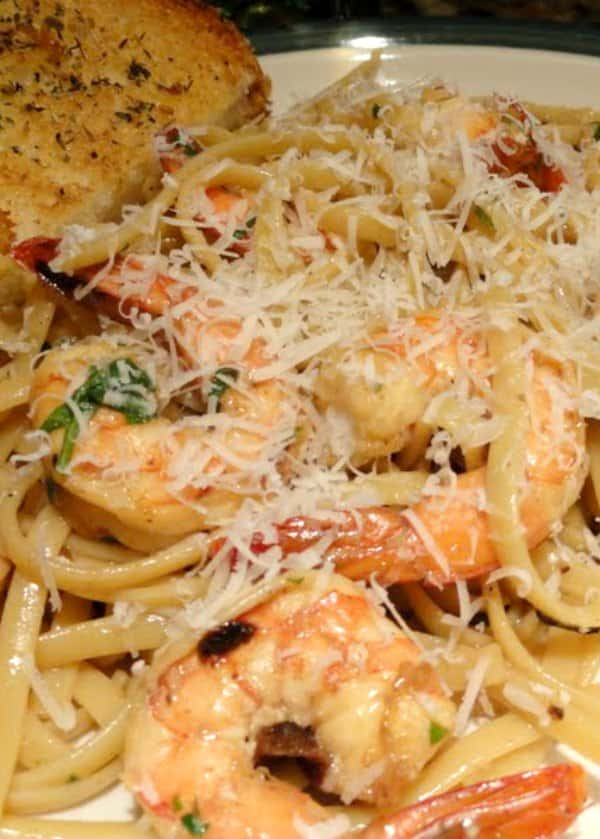 Shrimp Scampi recipe over Pasta in a lemon butter white wine sauce with parmesan cheese with a piece of garlic bread on side of plate from Serena Bakes Simply From Scratch.