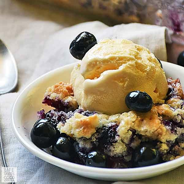 Blueberry Dump Cake with a scoop of vanilla ice cream in a white serving dish
