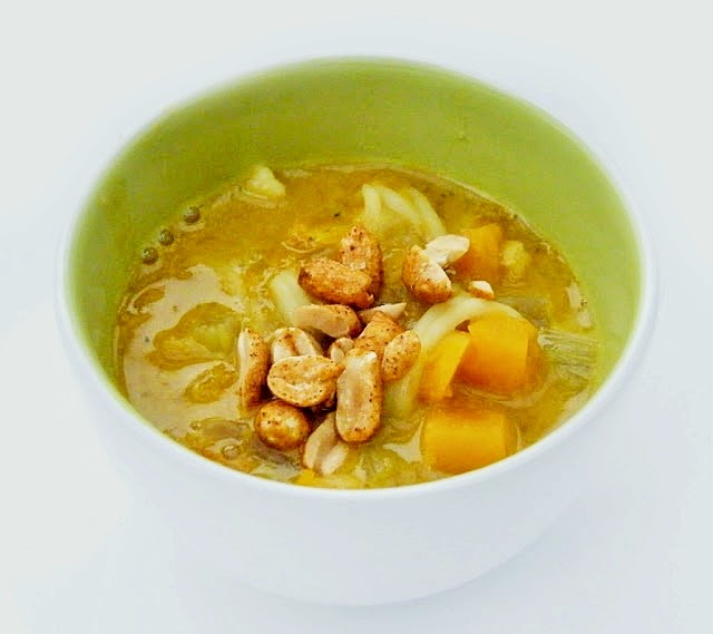 Squash, Carrot & Noodle Soup topped with roasted peanuts in a small white bowl