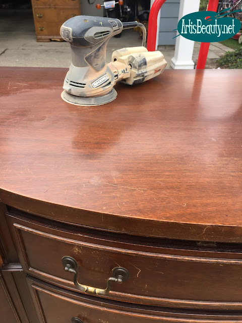 sanding the top of vintage bow front mahogany buffet using orbital sander