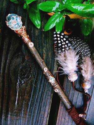 Bastão mágico confeccionado com madeira, o mesmo foi cuidadosamente decorado, é perceptível um cristal na ponta do bastão, isso é feito comumente para facilitar a canalização/direcionamento de energias através do cristal.