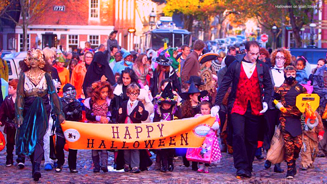 people in costumes holding a Happy Halloween banner for the parade