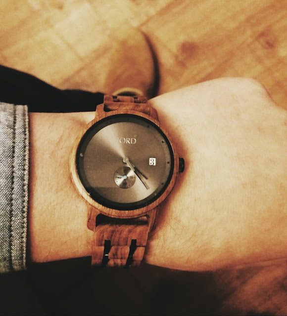 wooden watch on a mans left wrist