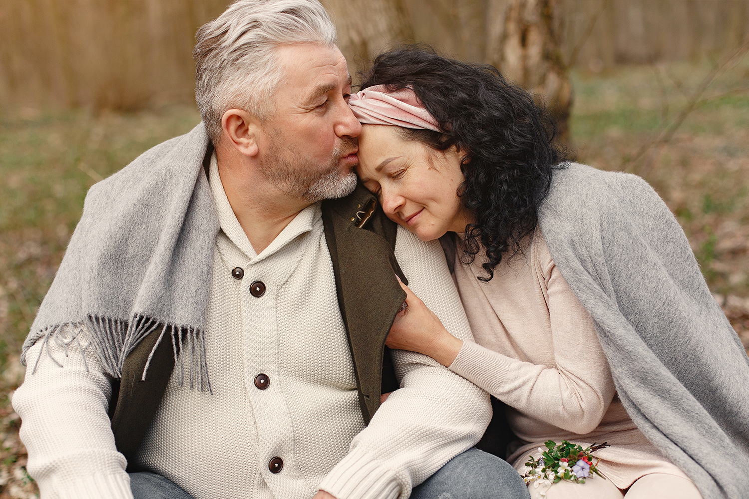 happy senior couple is hugging in the forest