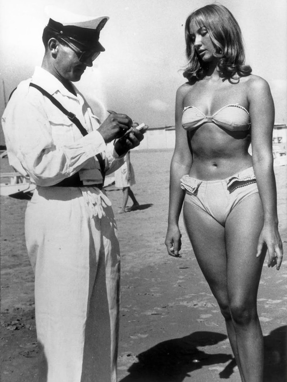 A police officer issuing a woman a ticket for wearing a bikini on an Italian beach '1957