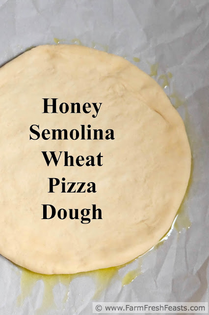 A recipe for basic pizza dough, with a bit of honey, semolina and wheat flours to make a nice chewy crust that stands up to whatever toppings you'd like to use.