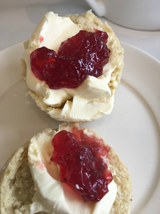 scone-with-cream-and-jam-spread-on-it