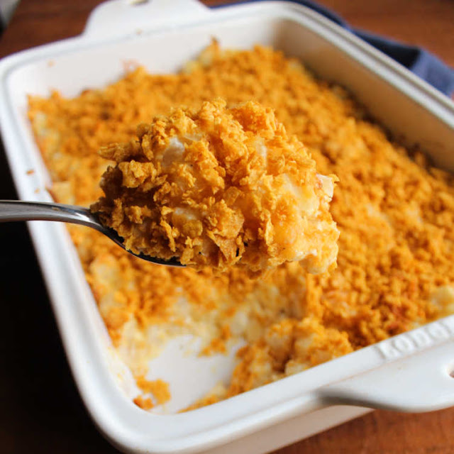 large spoonful of cheesy potato casserole with golden cornflake crumb topping