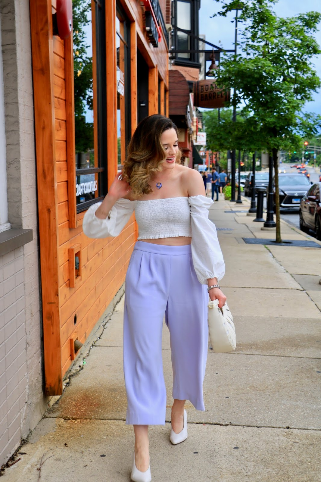 Nyc fashion blogger Kathleen Harper providing summer outfit inspiration by wearing a white off-the-shoulder crop top and high-waisted pants.