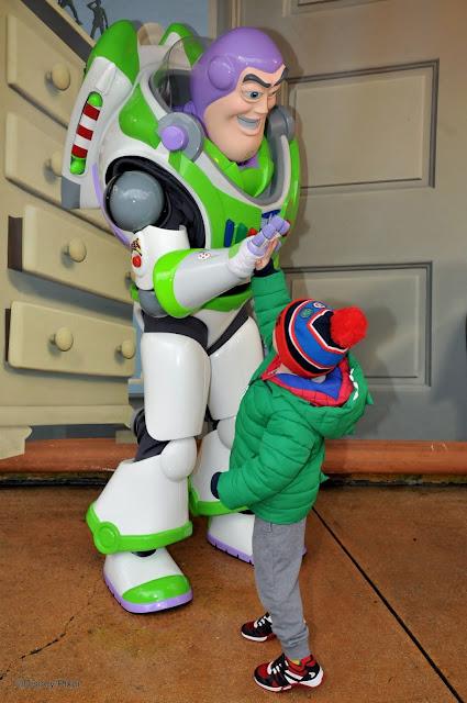 A little boy giving a high five to Buzz Lightyear