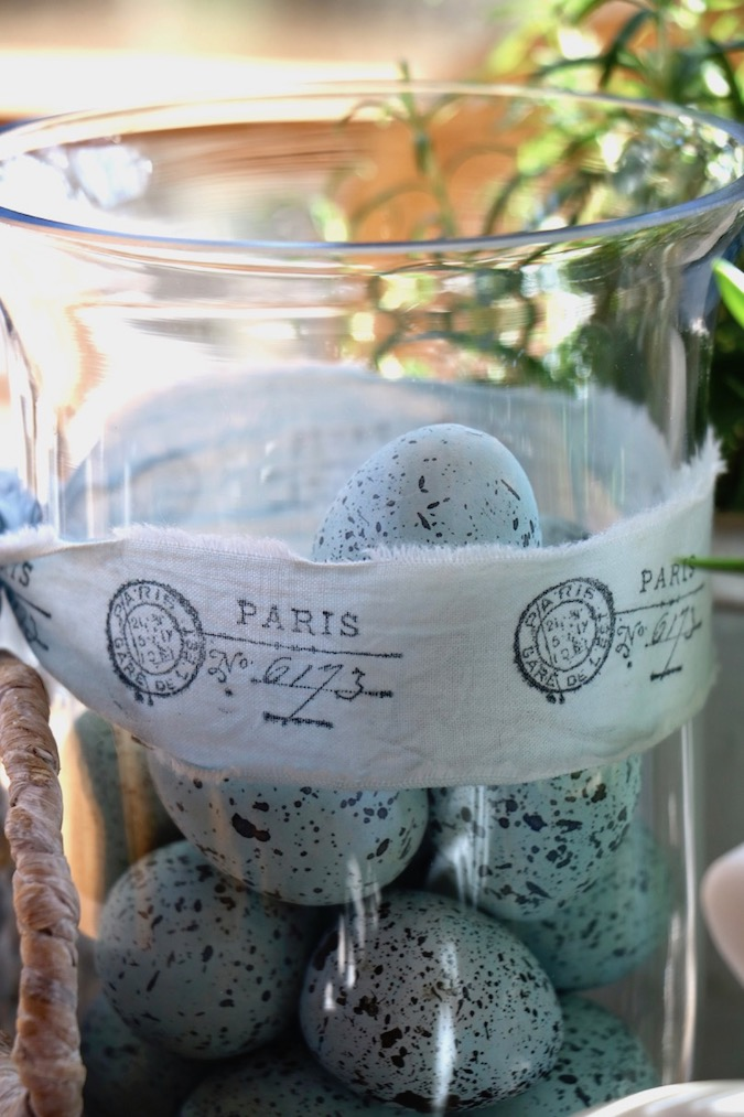 A clear vase tied with a handmade Paris fabric ribbon holds a set of blue speckled eggs in a Spring Blue and White Basket Arrangement