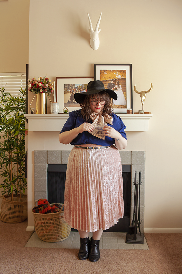 An outfit of a large black wool floppy hat, short sleeved navy blue blouse, pastel pink midi skirt and a pink lace scarf tied into an off center bow around the neck.