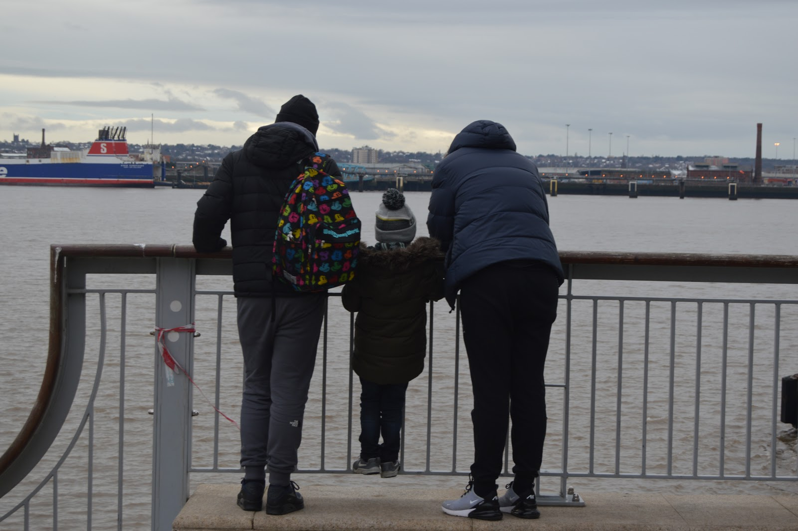 dad and two sons looking over the water