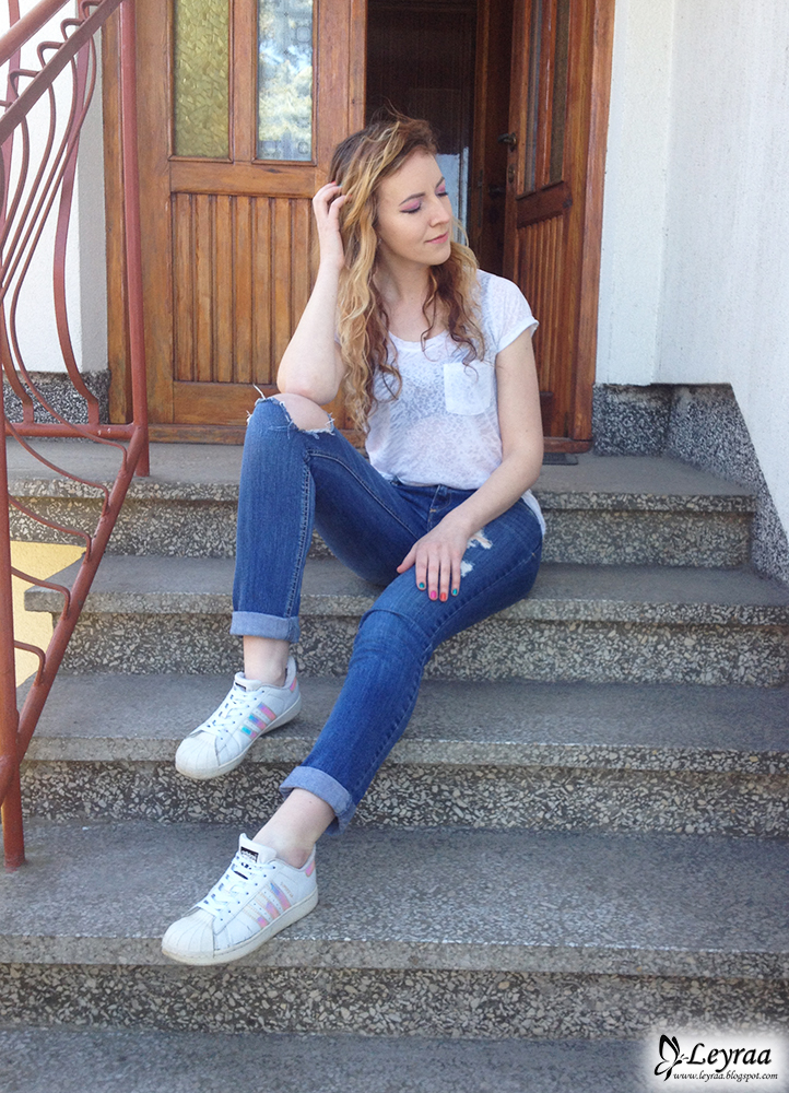 Czarny żakiet, biała lekko prześwitująca koszulka z kieszonką, jeansy 7/8 z dziurami, adidas superstar hologram