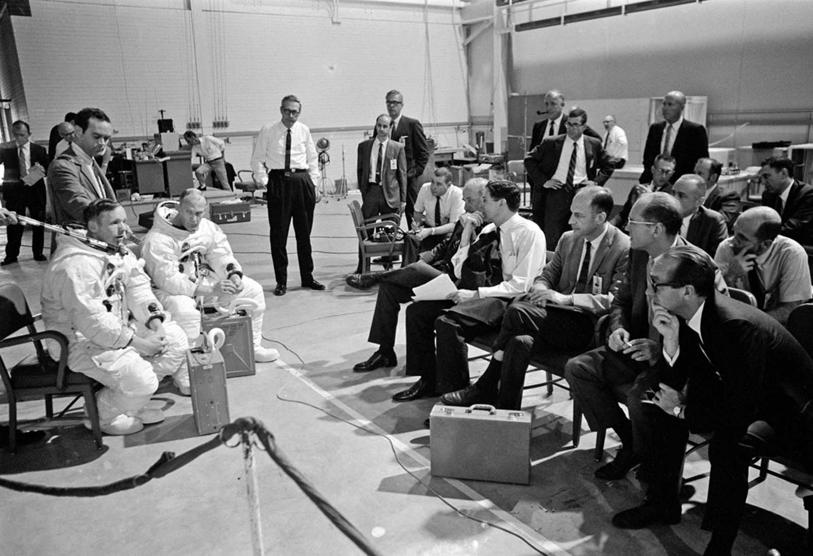 Neil Armstrong (left) and Buzz Aldrin brief NASA managers before a training session described in the crew-training summary as a