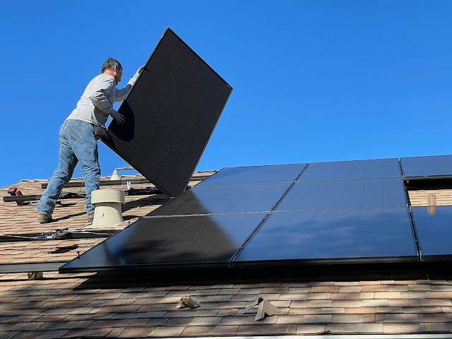 Worker fitting solar panels to roof:Photo by Bill Mead on Unsplash