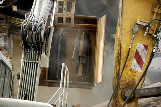 Fotografii toho, jak bagr vybírá poloprázdný šatník z demolovaného domu.