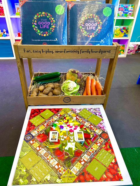 The Good Life board game aims to teach about sustainability  Image shows a board game a bit like monopoly, but covered in pictures of fruit and vegetables and with little wooden pieces to collect