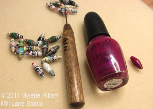 Assortment of unpainted paper beads, needle tool and burgundy nail polish