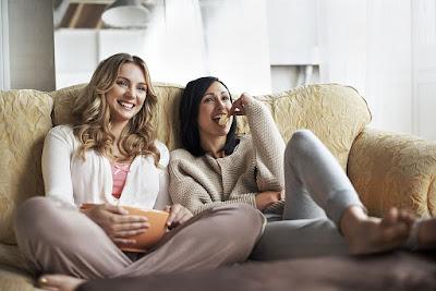 dve-lepe-devojke-jedu-grickalice-gledaju-seriju