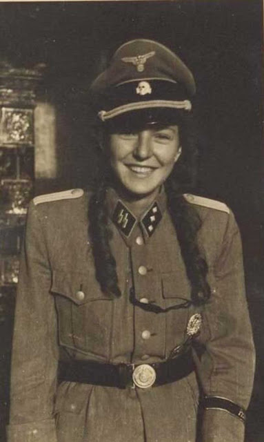 Nobody seems to know where this photo came from. It shows a young lady in an officer's (Untersturmführer) uniform. German soldiers for some reason found it kinky to dress their conquests in their uniforms. Note that the picture is cut off from showing the pants that she probably is not wearing. This may (or may not) be simply innocent girlish fun.