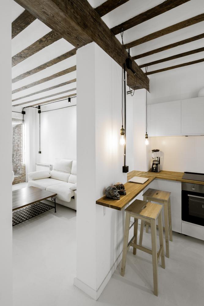 Cocina abierta blanco y madera en un espacio diáfano en el centro de Madrid