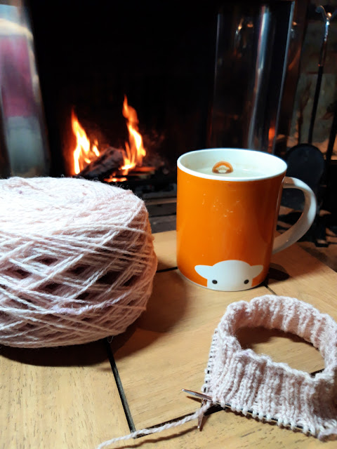 A small coffee table in front of an open fire.  There is a cake of pink yarn, a knitted sock cuff on a circular needle and an orange mug containing tea on the table.