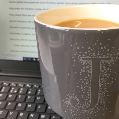 Grey mug in front of laptop