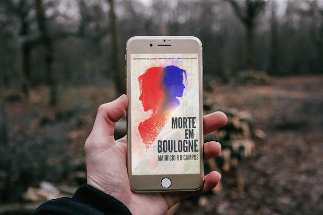 Uma pessoa segurando um celular em um bosque, na tela a capa do livro Morte em Boulogne