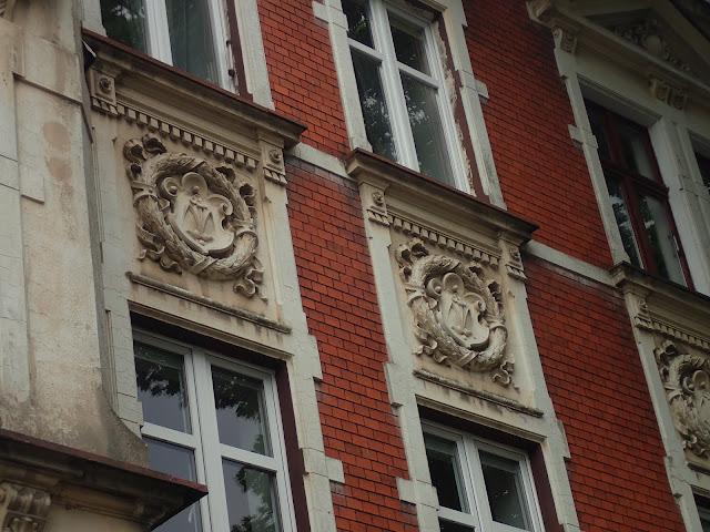 Budynki są ozdobione bliżej niezidentyfikowanymi herbami