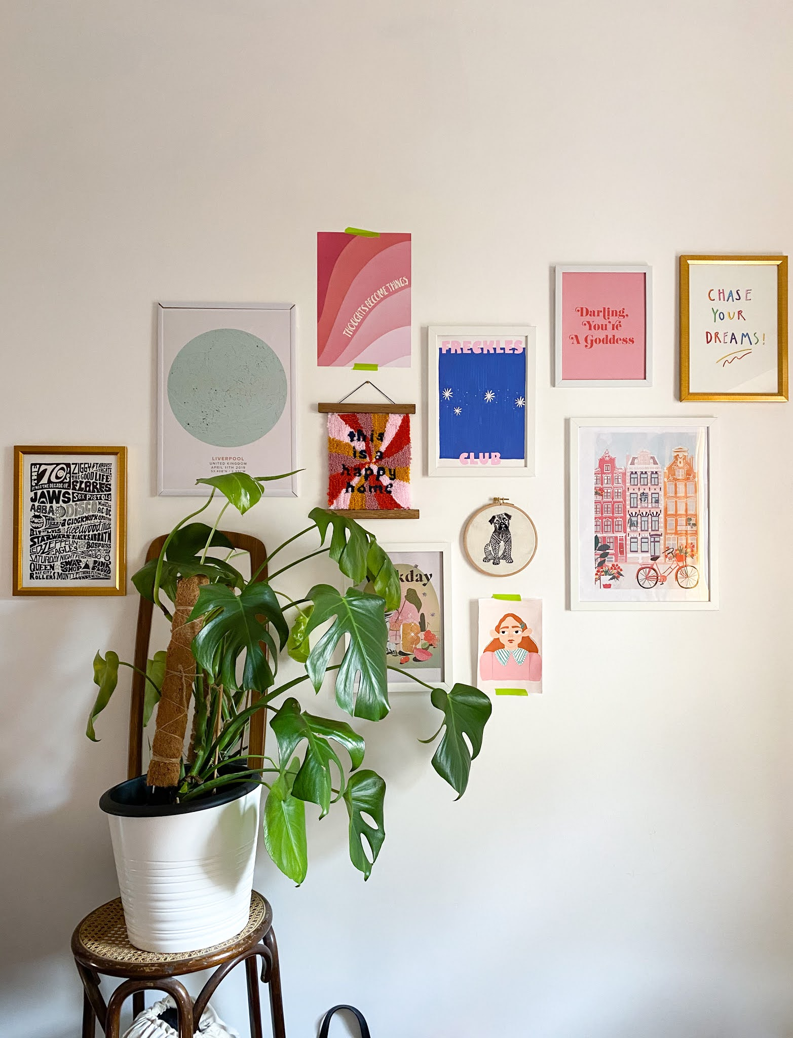 gallery wall of pink, orange and green prints and wall hangings on painted white bedroom wall. A dark wood and rattan stool holds a large monstera plant against a teak wood 70s style mirror