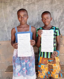 Sisters displaying birth certificates in Cameroon Africa.