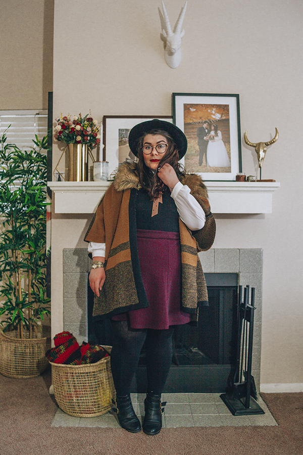 An outfit of a black wide brim fedora, brown faux fur collar poncho, peter pan collar blouse, black sleeveless dress, purple chevron print skater skirt, black tights and black heeled buckle boots.
