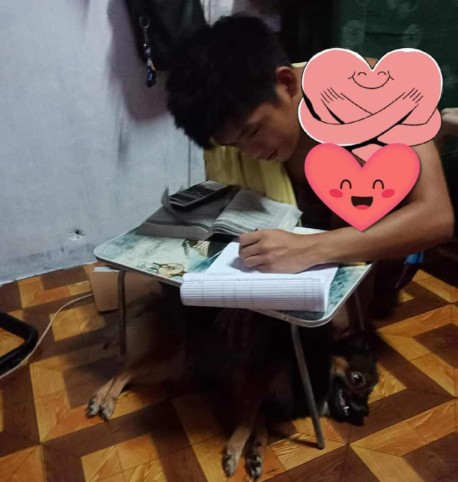 CE Top 2 Jeremy Rifarael studies in a small table with his pet dog