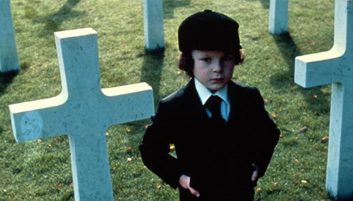 """Imagem: Personagem do filme """"A profecia"""". Garoto branco de cerca de 10 anos, usa sobretudo e boina preta. Ele esta parado com as mãos no bolso parado no  meio de um cemitério a luz do dia. Ao seu redor tem cruzes brancas cravadas no chão."""