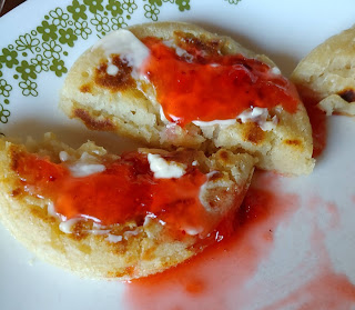 Crumpet with buter and jam on a plate.