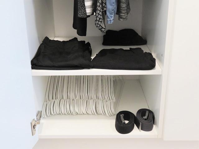 Toiseksi alimmalla hyllyllä on housut ja alimmalla hyllylä tällä hetkellä läjä käyttämättömiä hengareita sekä kaksi vyötä.