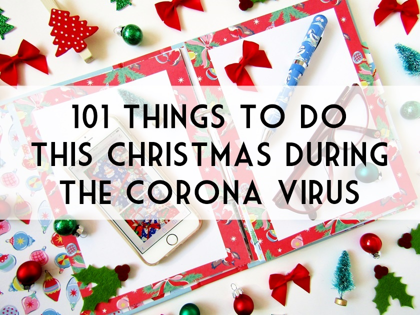 A photo of a Christmas flat lay taken from above, partially showing an open Christmas organiser, topped with a pen and phone, and surrounded by small Christmas decorations, beneath a header in black and white saying '101 Things To Do This Christmas During The Corona Virus.'
