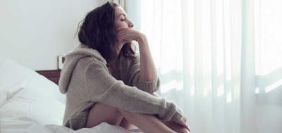 Mujer joven sentada en la cama, pensando, con una sudadera beige con gorro.