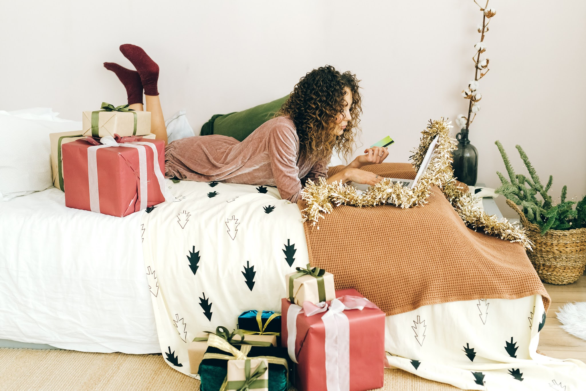 Woman doing online shopping on her bed surrounded by parcels. Image by  Photo by Olya Kobruseva from Pexels
