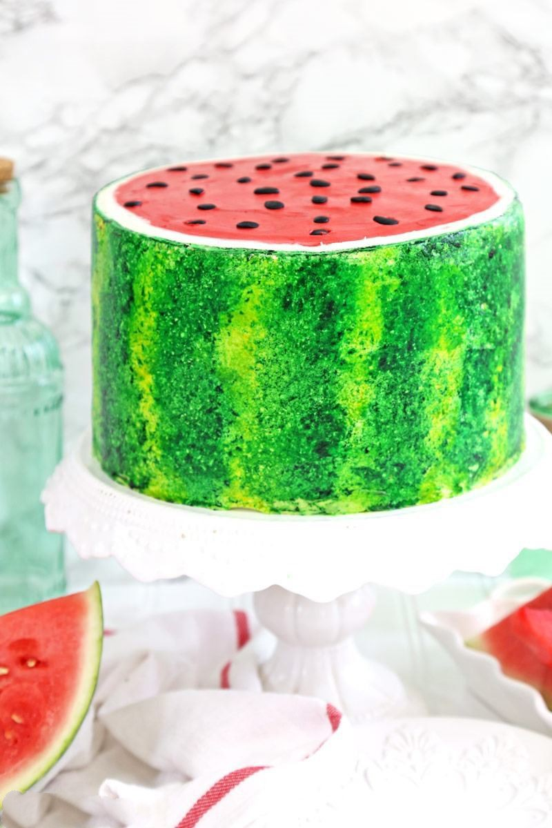 Watermelon Layer Cake Video - This Watermelon Layer Cake is the ultimate summer dessert! Layers of watermelon-flavored cake are studded with mini chocolate chips, and the outside is painted to look just like a watermelon.