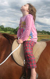 girl sitting on a horse, face upraised, eyes closed