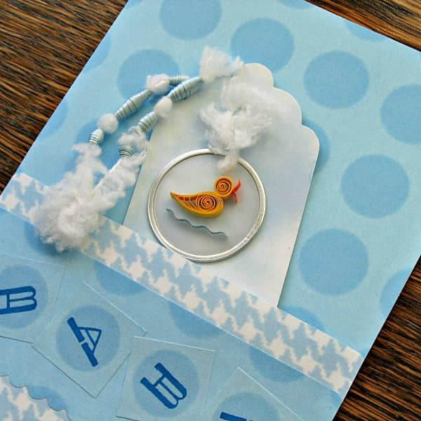 baby card with quilled duckling attached with fuzzy white yarn threaded onto paper beads