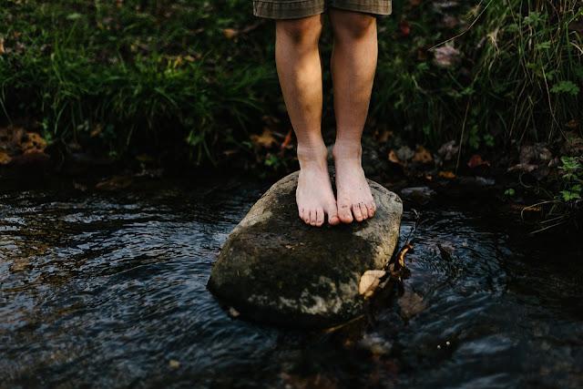 Kind steht auf Stein am Fluss