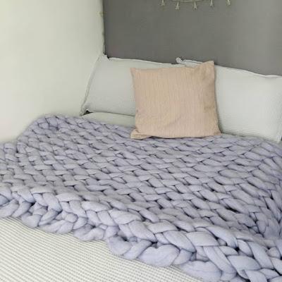 purple knit blanket on a bed.