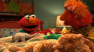 Louie begins to put Elmo in his bed. Sesame Street Bedtime with Elmo